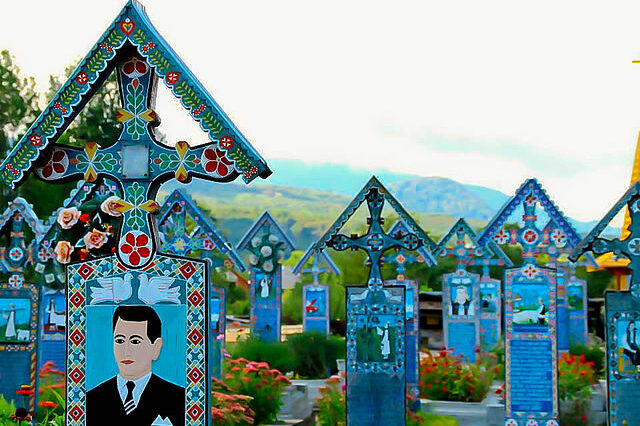 A collection of blue painted crosses in the Merry Cemetery with a cartoon-like painting of a man on the front of the primary cross with greenery and flowers in the background